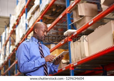 Businessman With Digital Tablet In Warehouse - stock photo