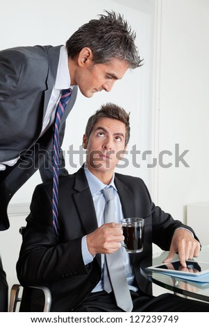 Businessman with digital tablet showing something to colleague at desk in office