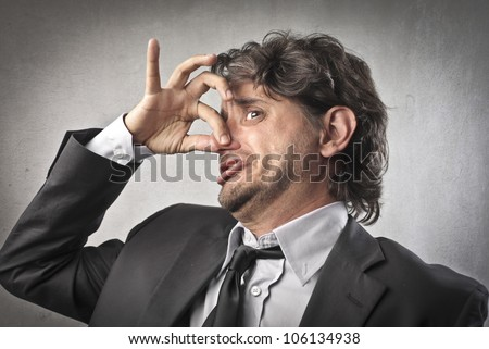 Businessman with disgusted expression closing his nostrils with his fingers - stock photo