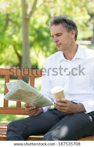Businessman with disposable cup reading newspaper in the park - stock photo
