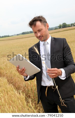 Businessman with electronic tablet standing in wheat field - stock photo
