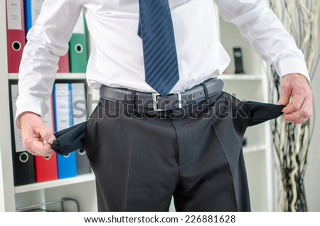 Businessman with empty pockets at office - stock photo