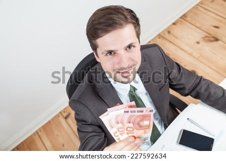 businessman with 30 euro holding in hand - stock photo