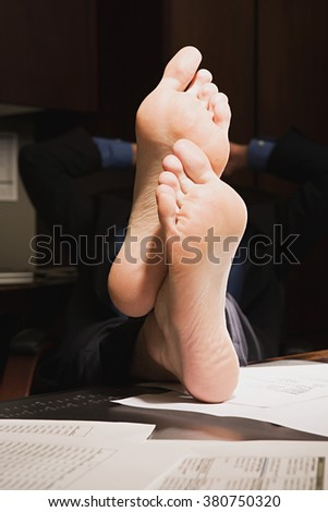 Businessman with feet up on desk - stock photo