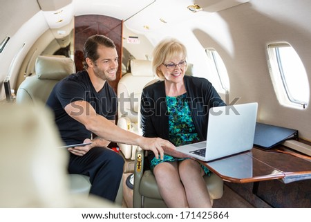 Businessman with female colleague discussing over laptop on private jet - stock photo