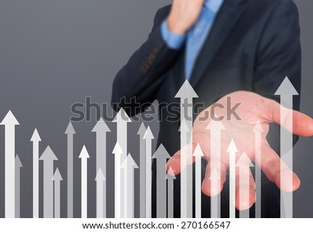 Businessman with financial symbols coming. Business, growth, investment concept. Man hand showing arrows. Isolated on grey. Stock Image
