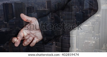 Businessman with fingers crossed against view of cityscape - stock photo