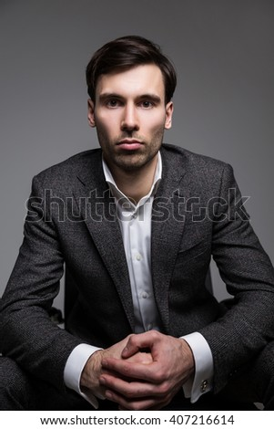 Businessman with fist in palm on dark background