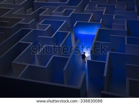 Businessman with flashlight walking through maze - stock photo