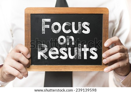 Businessman with focus on results words. Businessman holding board on the background with focus on results words
