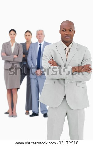 Businessman with folded arms and team behind him against a white background - stock photo