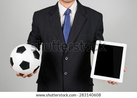 businessman with football and tablet - stock photo