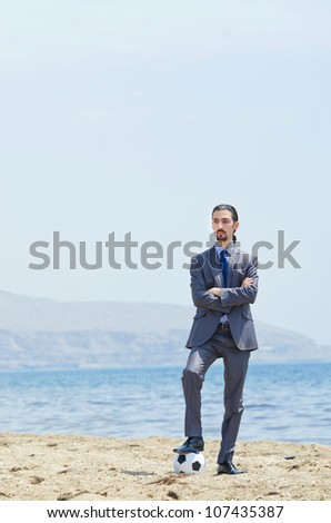 Businessman with football on beach