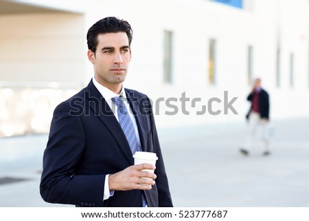 Businessman with formal clothes drinking coffee to go with a take away cup. Man wearing blue suit and tie in urban background.