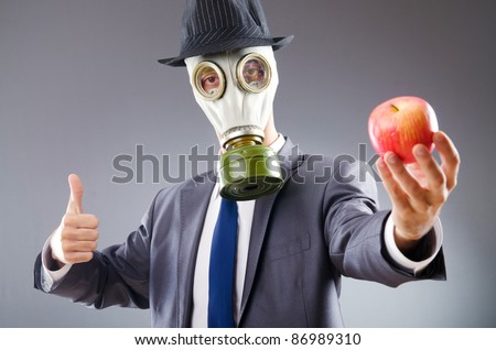 Businessman with gas mask and apple - stock photo
