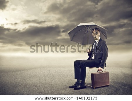 businessman with gas mask and umbrella sitting alone in the desert