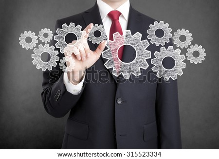 Businessman with gears, concept of well organized work process.  - stock photo