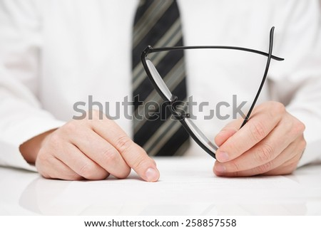 Businessman with glasses in hand is carefully reading contract - stock photo
