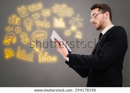 Businessman with glasses using his tablet against grey background - stock photo