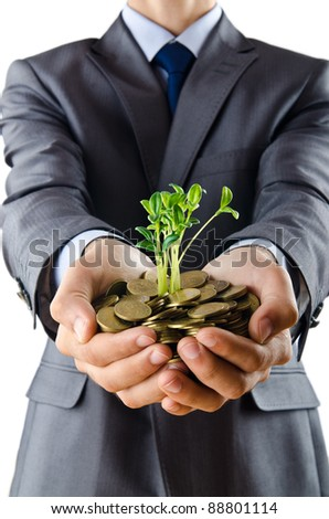 Businessman with gold seedlings and coins - stock photo