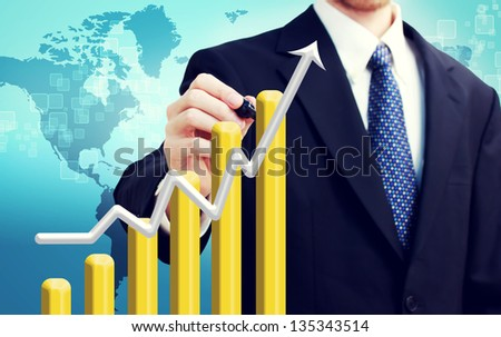 Businessman with graph representing growth with world map backdrop - stock photo
