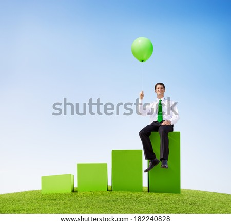 Businessman With Green Balloon On Graph - stock photo