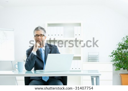 Businessman with grey hair, wearing grey suit and glasses thinking over laptop computer, sitting at desk in bright, modern office, leaning on hand, smiling. - stock photo
