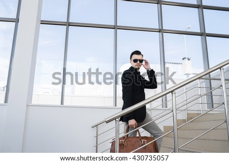 Businessman with hairstyle in sunglasses holding bag while walking on stairs
