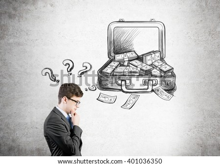 Businessman with hand at chin, open case with money drawn on concrete wall behind, question marks over his head. Side view. Concept of making money. - stock photo