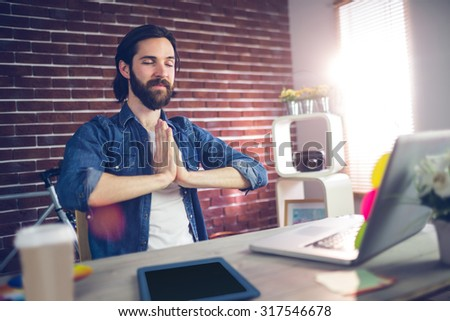 Businessman with hand clasped doing yoga in creative office - stock photo