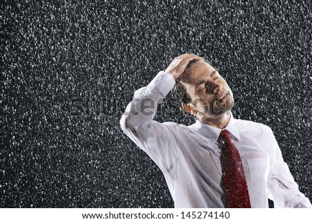 Businessman with hand on wet hair and eyes closed in the rain - stock photo