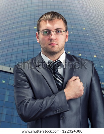 Businessman with hand over heart against office building - stock photo