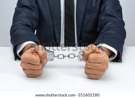 Businessman with handcuffs - stock photo