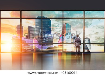 Businessman with hands in pockets standing at panoramic window. Office, night. Moscow city view. Double exposure. Concept of thinking. - stock photo