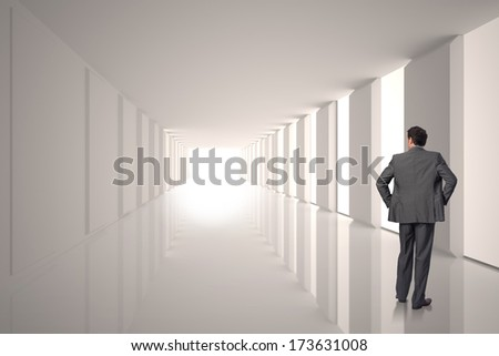 Businessman with hands on hips against lit up white modern hallway