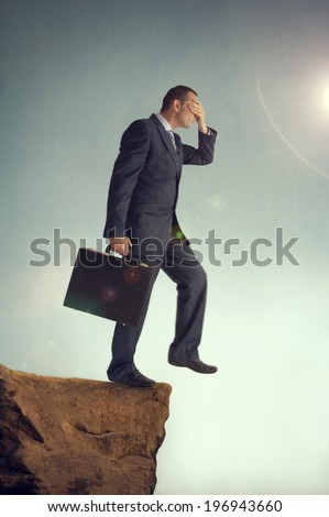 businessman with hands over eyes steps off a cliff - stock photo