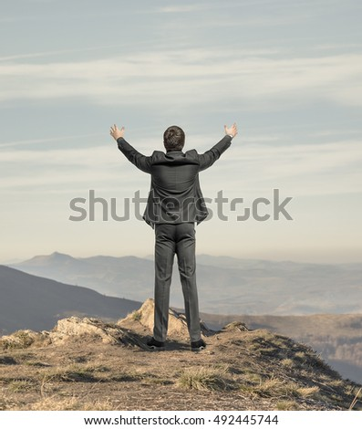 Businessman with hands raised standing at the edge of a cliff on the background of mountain scenery. Freedom concept.