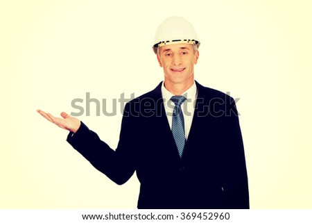 Businessman with hard hat holding copyspace - stock photo