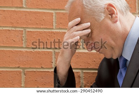 Businessman With Head In Hand - stock photo