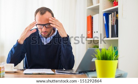 Businessman with headache sitting in his office. - stock photo