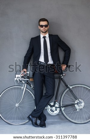 Businessman with his bicycle. Full length of handsome young businessman leaning at the bicycleand looking at camera while standing against grey background - stock photo