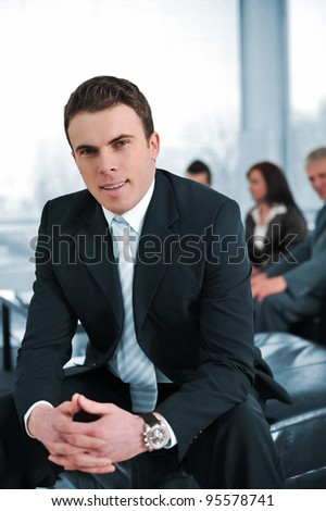 Businessman with his co-workers in office smiling, looking at camera - stock photo