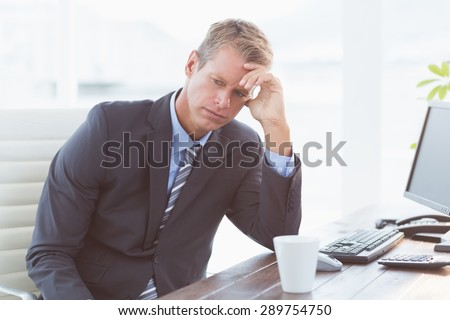 Businessman with his hand on his forehead in his office - stock photo