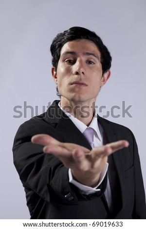 Businessman with his hand open to you (selective focus) - stock photo
