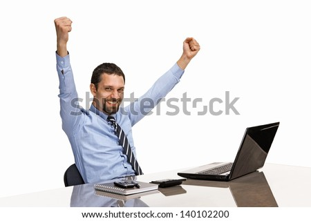 businessman with his hands raised while working on laptop  - stock photo