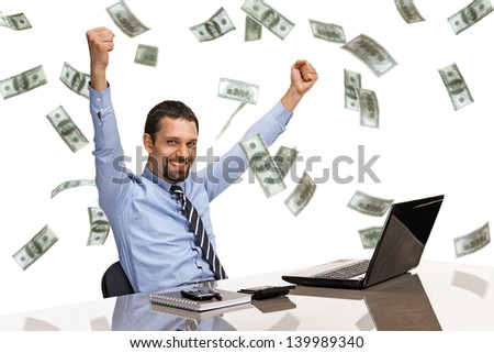 businessman with his hands raised while working on laptop with money rain  - stock photo