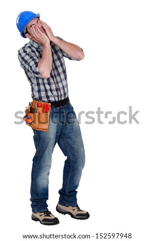 Businessman with his hands to his face - stock photo