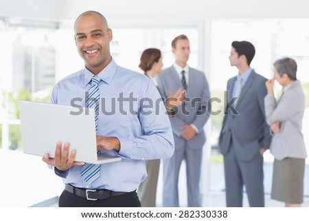 Businessman with his laptop and his colleagues behind in the office - stock photo