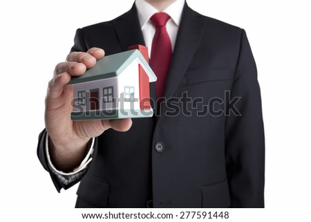 Businessman with house miniature in hand isolated on white - stock photo