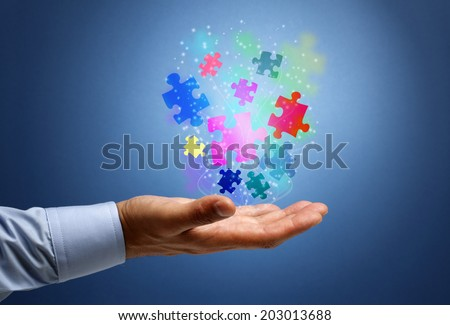 Businessman with illuminated flying puzzle pieces concept for solution, business strategy and creativity - stock photo